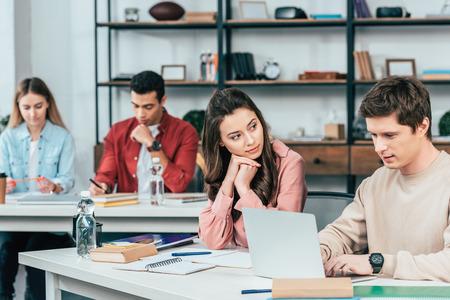 Studenti multietnici seduti alla scrivania e che usano il laptop mentre studiano in classe