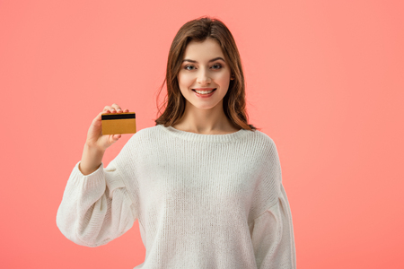 smiling brunette girl holding credit card isolated on pink