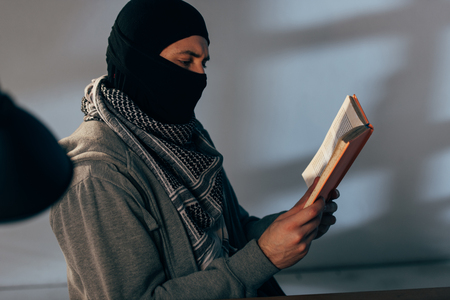 Terrorist in black mask and keffiyeh scarf reading book