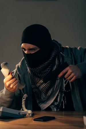 Angry criminal in mask aiming gun and looking at handset