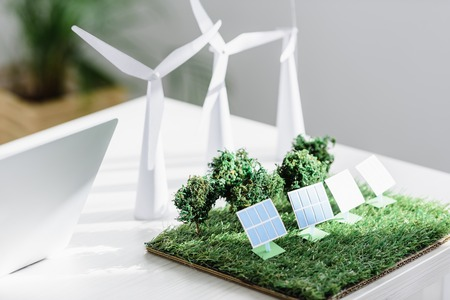 table with trees, windmills and solar panels models on grass in office Stock Photo