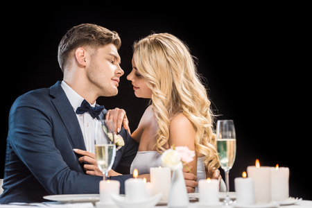 happy couple hugging while sitting at served table isolated on black