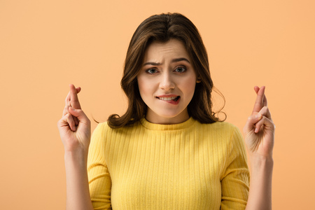 attractive brunette woman biting lips while standing with fingers crossed  isolated on orange Banque d'images - 120338611