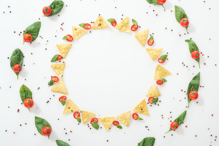 flat lay with tasty nachos, spices and sliced chili peppers with basil leaves and ripe cherry tomatoes Stock Photo