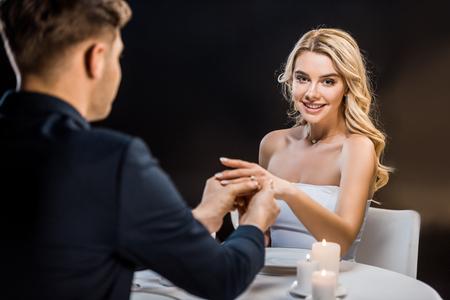 El novio joven poniendo el anillo de bodas en el dedo de novias sobre fondo negro