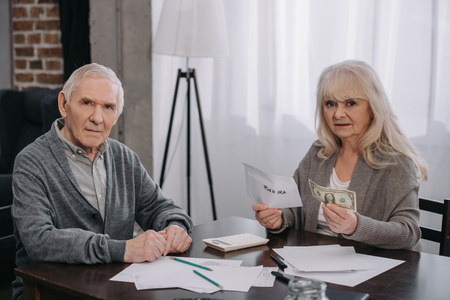 senior couple holding money, envelope with roth ira lettering and looking at camera