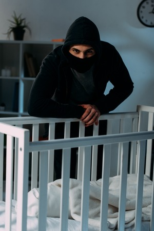 Criminal in mask and hoodie standing near crib in dark room Stock Photo