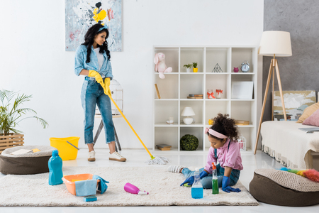 cute african american child cleaning carpet while mother washing floor with mop