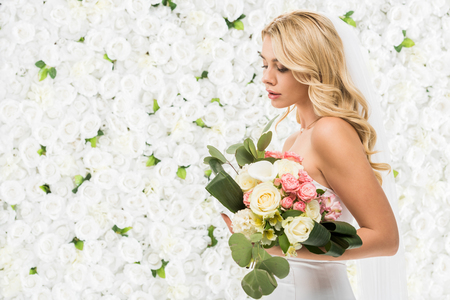 beautiful young bride holding wedding bouquet on white floral background