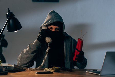 Terrorist in mask holding dynamite and talking on phone