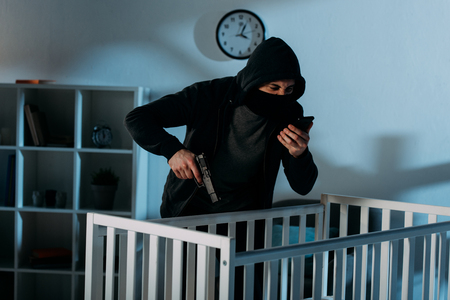 Angry criminal talking on smartphone and aiming gun in crib Stock Photo