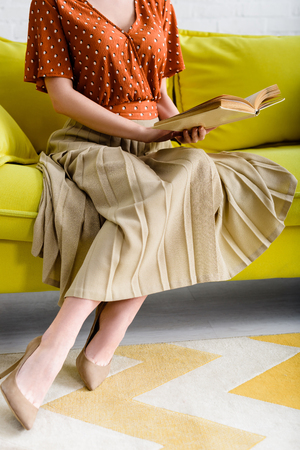 cropper view of fashionable woman in heeled shoes sitting on yellow sofa and reading book