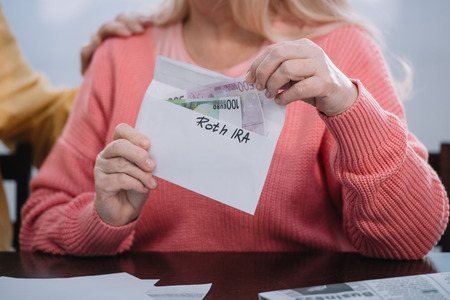 partial view of woman holding envelope with 'roth ira' lettering and money Stock Photo - 120338211
