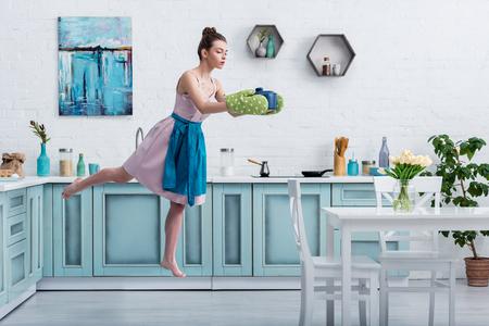 Hermosa niña descalza en agarraderas levitando en el aire con olla en la cocina