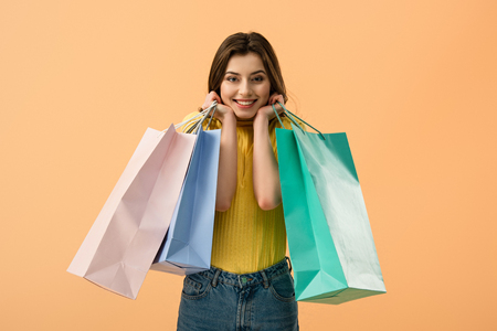 Blissful brunette young woman holding shopping bags isolated on orange