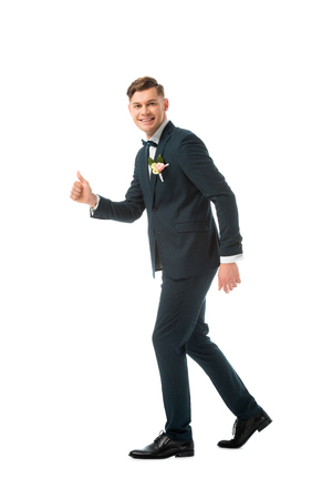 cheerful bridegroom in black suit showing thumb up isolated on white Stock Photo