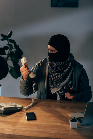 Terrorist in black mask holding gun and looking at handset