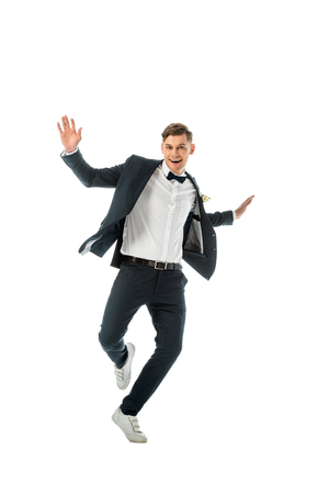 handsome excited groom dancing and looking at camera isolated on white