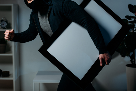 Partial view of thief stealing flat-screen tv with blank screen