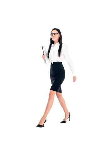 Full length view of confident businesswoman in skirt walking isolated on white