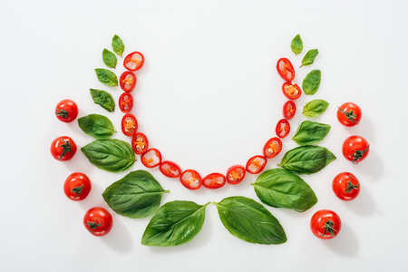 flat lay with cut chili peppers, basil leaves and ripe cherry tomatoes on white background with copy space Stock Photo