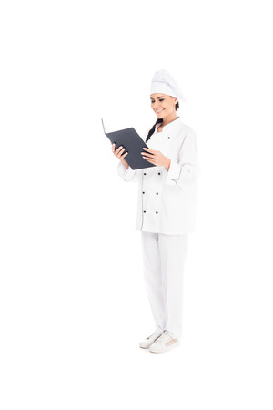 Full length view of smiling chef in uniform reading book isolated on white