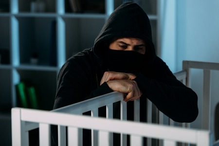 Sad kidnapper in mask and hoodie looking in crib