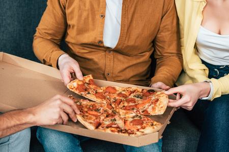 Vista recortada de tres amigos alegres sentados en el sofá y comiendo pizza juntos Foto de archivo