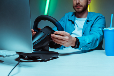 selective focus of cyber sportsman playing video game with steering wheel Фото со стока