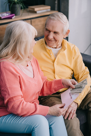 smiling senior couple holding envelope with 'roth ira' lettering and dollar banknotes Stock Photo - 120337777