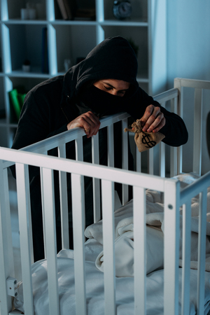 Kidnapper in mask and black hoodie holding money bag and looking in crib