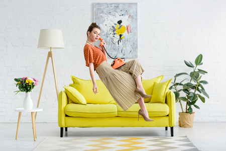 elegant young woman levitating in air and talking on vintage phone in living room Stok Fotoğraf