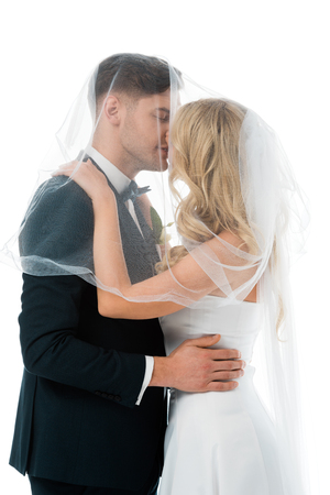 bride kissing groom while covering him with bridal veil isolated on white