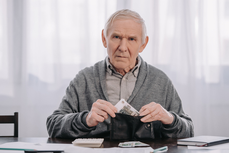 male pensioner sitting at table and putting money in wallet while looking at camera
