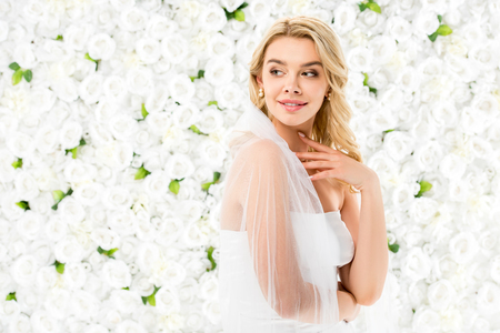 beautiful smiling young woman with blonde hair posing at camera on white floral background 스톡 콘텐츠