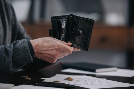 selective focus of male pensioner sitting at table with paperwork and counting money