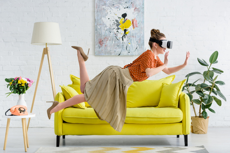 side view of elegant young woman levitating in air while wearing virtual reality headset Stok Fotoğraf