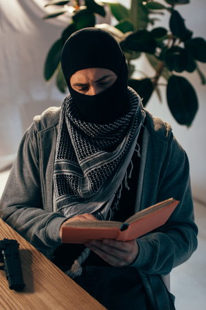 Serious terrorist in black mask reading book at table Stock Photo