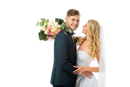 happy bride with wedding bouquet hugging smiling groom isolated on white Stock Photo