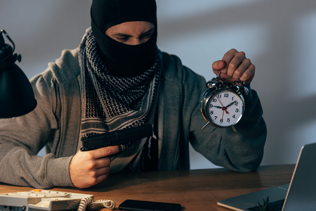 Angry terrorist in mask holding pistol and looking at alarm clock