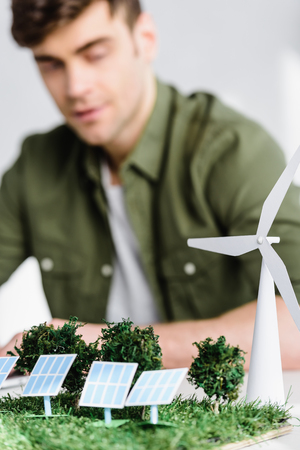 selective focus of architect at table with windmill, trees, solar panels models in office Standard-Bild