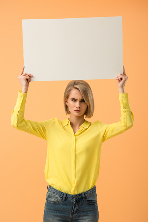 Dissatisfied blonde girl in yellow shirt holding blank placard isolated on orange