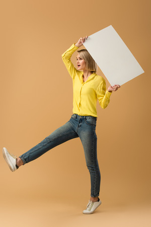 Full length view of blonde woman in jeans standing on one leg and holding blank placard on beige background Archivio Fotografico