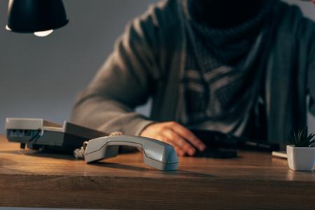 Vista recortada del terrorista sentado a la mesa con teléfono