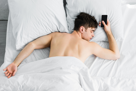 handsome man sleeping under blanket near smartphone with blank screen on bad