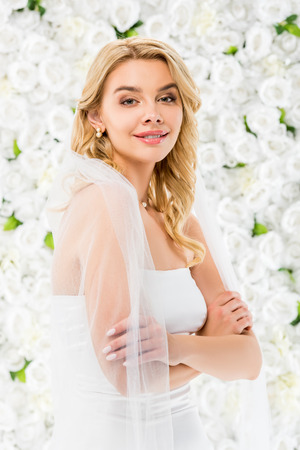 smiling beautiful bride with crossed hands looking at camera on white floral background