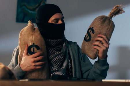 Terrorist in mask holding bags with dollars in room Stock Photo