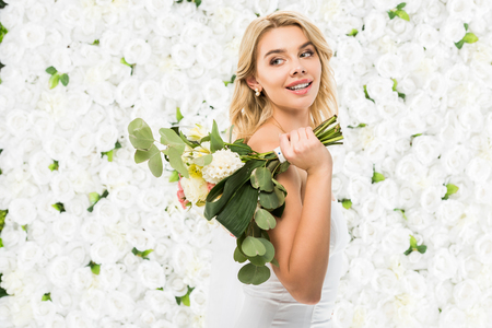 beautiful bride holding wedding bouquet on white floral background