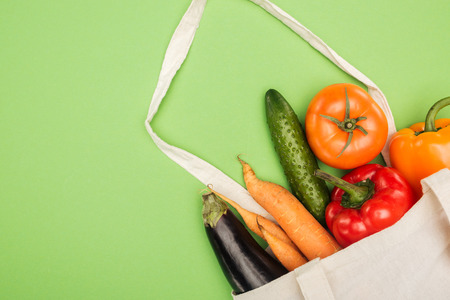 cotton bag with fresh ripe vegetables on light green background Фото со стока