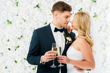 happy young groom and bride standing face to face and holding glasses of champagne on white floral background Stock Photo